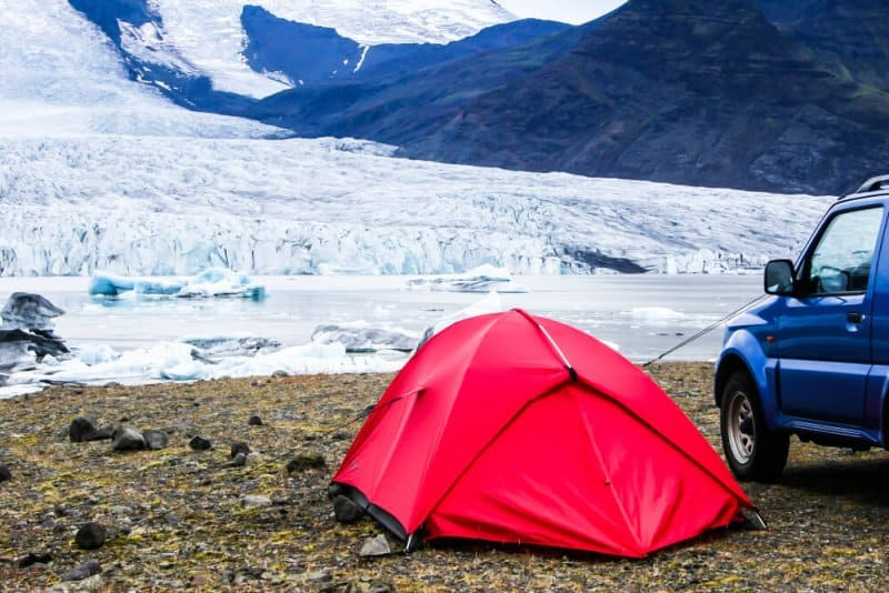 Red tent set by a glaciar lake, snow can easily be seen while camping in February in Iceland