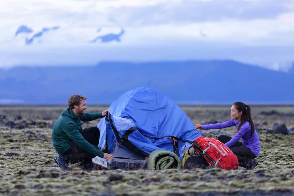 Couple setting a tent, a cheap option if camping on a budget