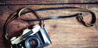 Retro camera on vintage wooden background showing best photography in Iceland concept