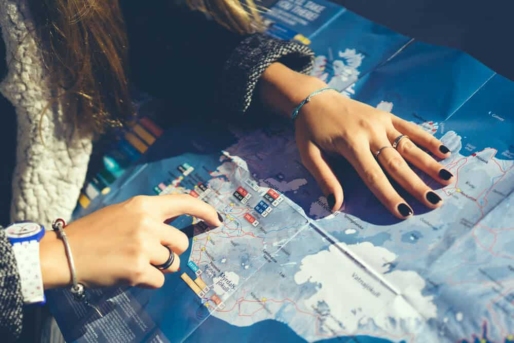 girl checking her itinerary on her road trip map of Iceland