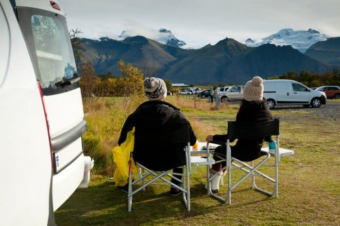 Couple enjoying the views at a camping during their camper road trip in Iceland