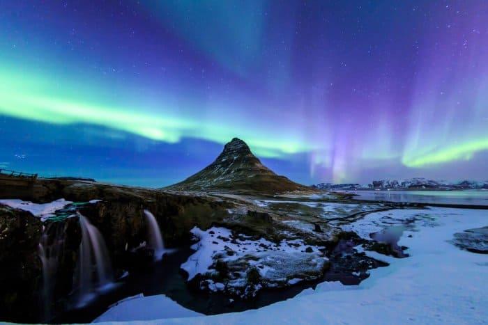 Iceland's Aurora Borealis as a backdrop to Kirkjufell mountain and Kirkjufellsfoss waterfall