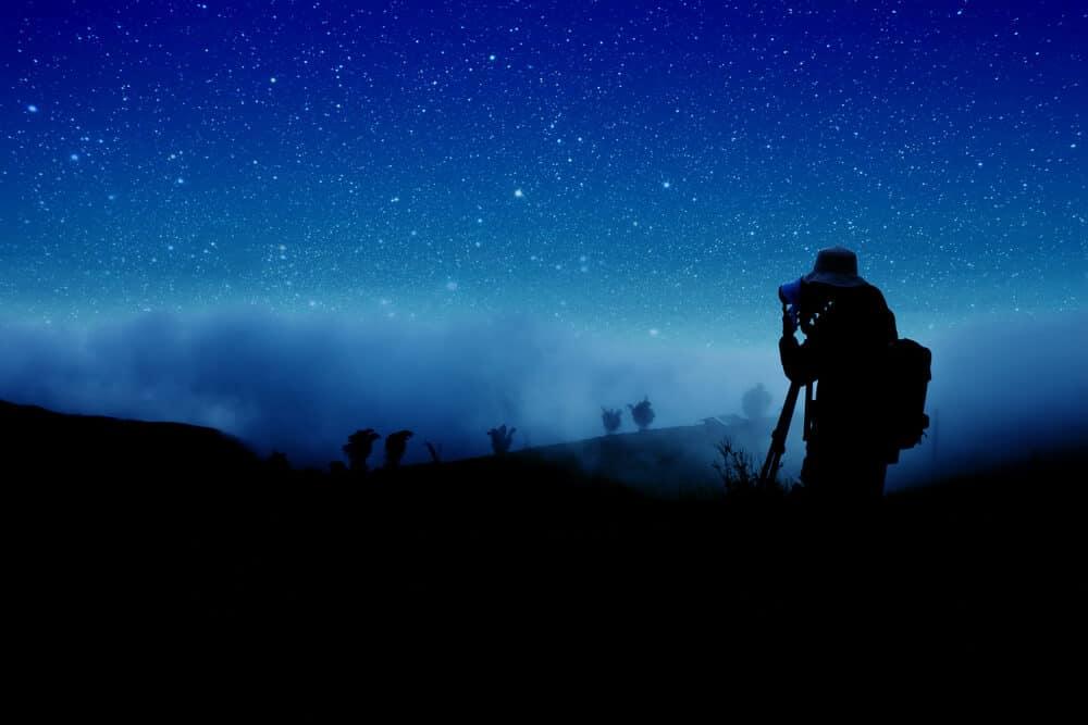 Man preparing to take photos of a starry night sky
