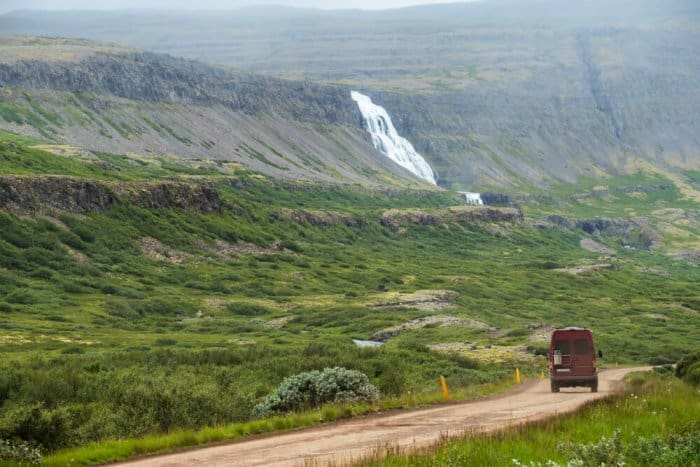 Van on a road trip through Iceland with a waterfall on the background