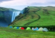 Multiple tents set up at Skógafoss waterfall for camping in Iceland in September