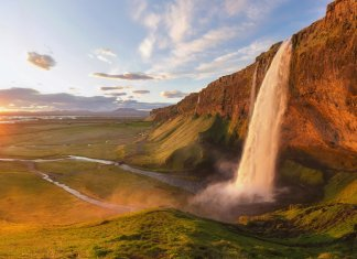 Midnight sun in Iceland on the horizon with a waterfall
