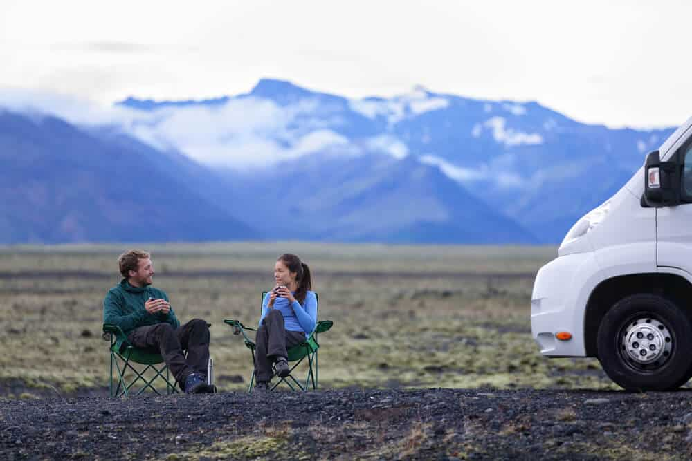 Couple relaxing with their motorhome while camping in Iceland