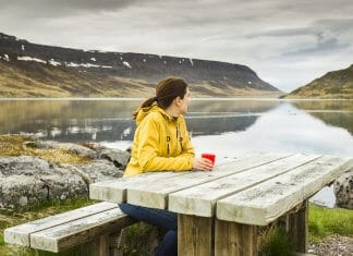Woman looking out at water and hills from bench at campground in Iceland