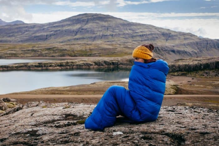 Woman staying warm in blue sleeping bag in Icelandic Highlands while camping