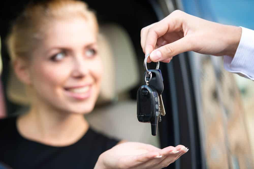 Woman receiving the keys to her Iceland car rental