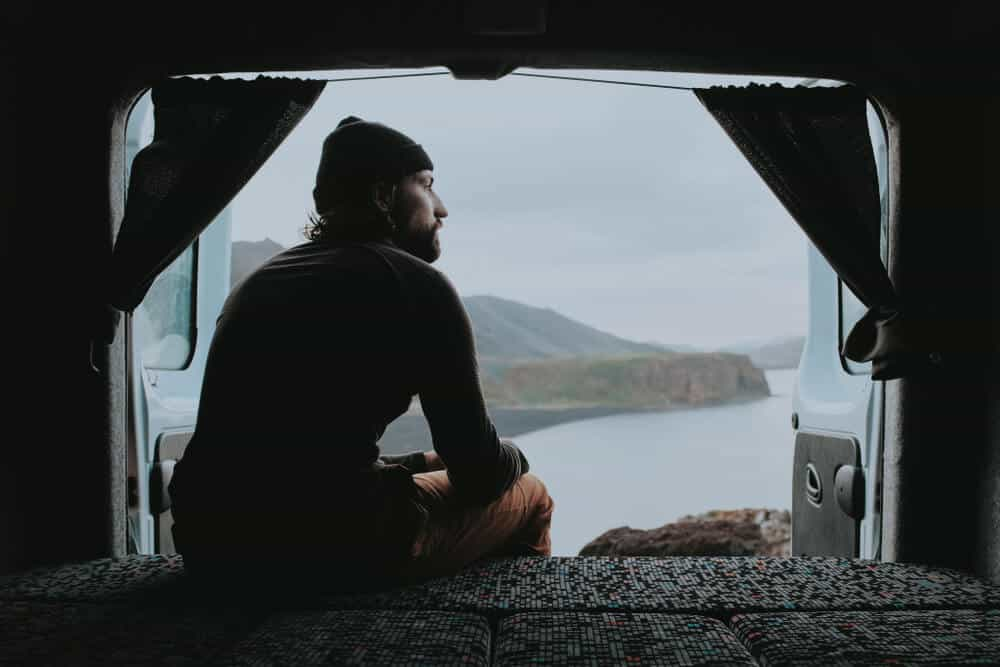 Man looking out from his campervan rental in Iceland