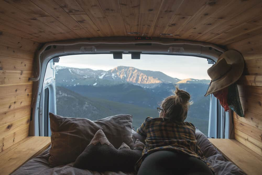 Woman looking out at mountains from campervan during Iceland road trip