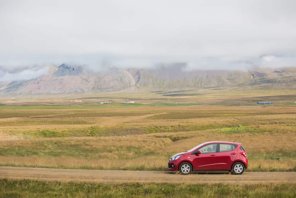 Red rental car in Iceland driving past beautiful landscapes