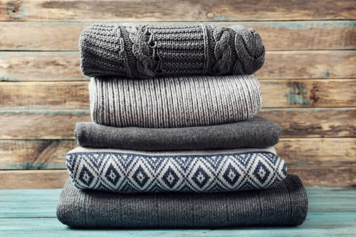 Pile of winter sweaters to pack for suitcase for Iceland trip