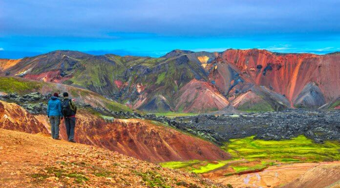 Two hikers stop to admire the beautiful rhyolite mountains in Landmannalaugar