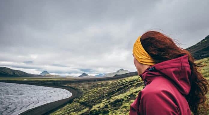 Female tourist looking at the mossy landscape while camping in Iceland