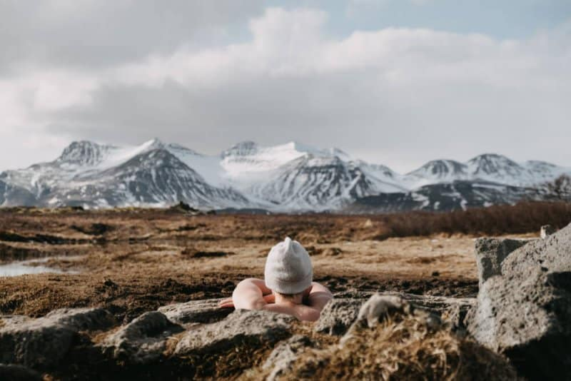 Tourist relaxing in a hot pot in Iceland admiring winter scenery