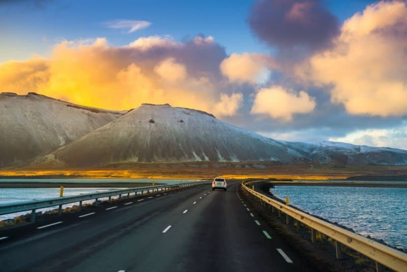 Driving down the road in Iceland with snowy winter mountains in the background