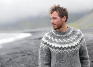 Handsome Icelandic man having a walk along the black sand beach in Iceland