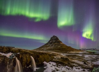 Winter landscape in Iceland with the Northern Lights dancing in the sky
