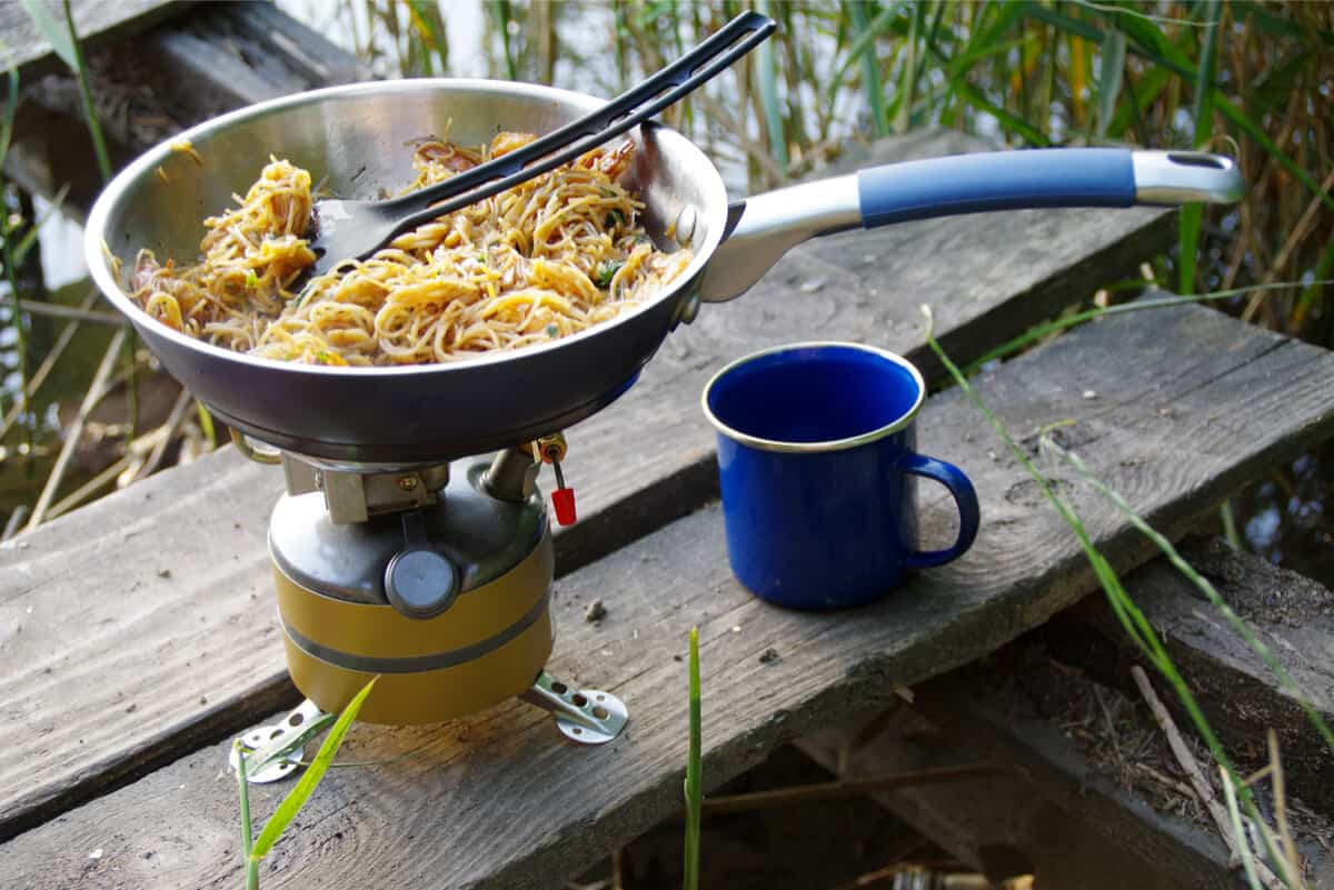 Skillet cooking dinner over camping stove