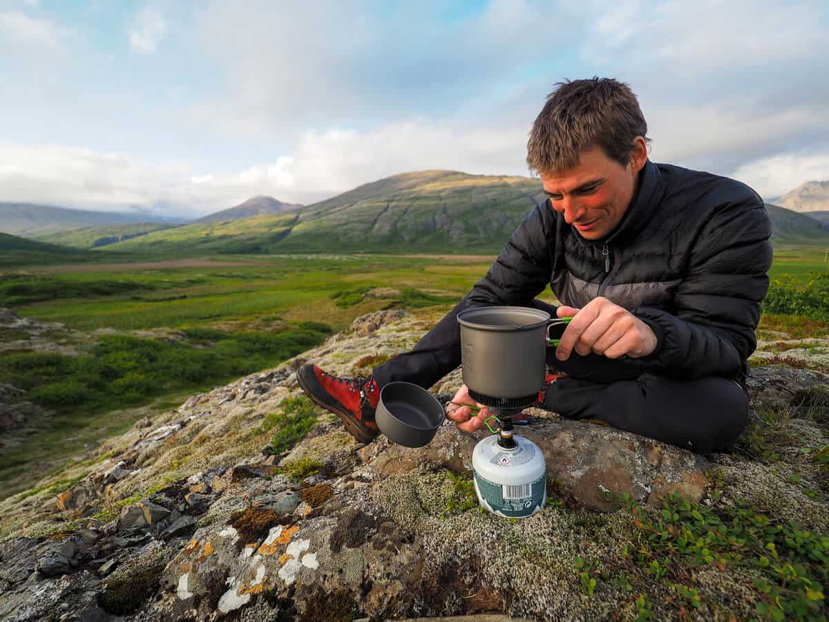 Man cooking over gas camping pot in Iceland
