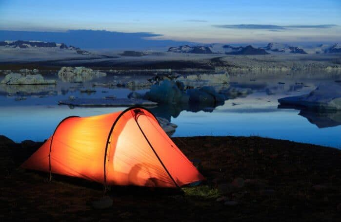 Red tent over Jokulsarlon lagoon, Iceland at dusk while camping in Iceland in November