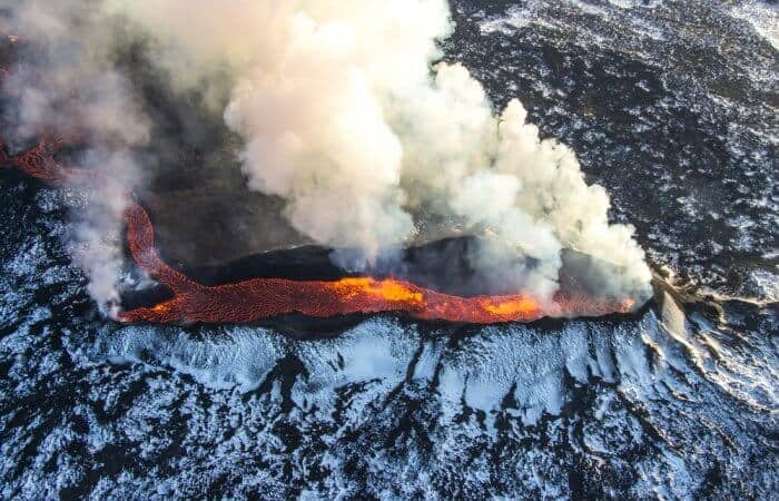 Volcano in Iceland producing smoke and hot melted lava