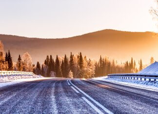 Icy winter road with mountains in background