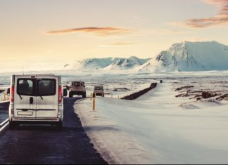 Campervan on the ring road with snow on the shoulder and a pink sky