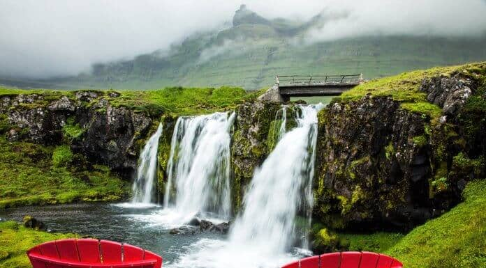 Two red chairs overlooking a waterfall in Iceland during summer season