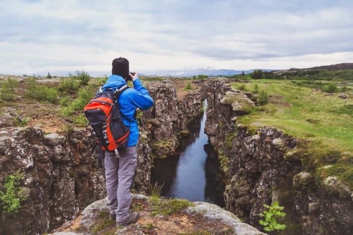 Visitor taking a photo to the landscape of Thingvellir National Park