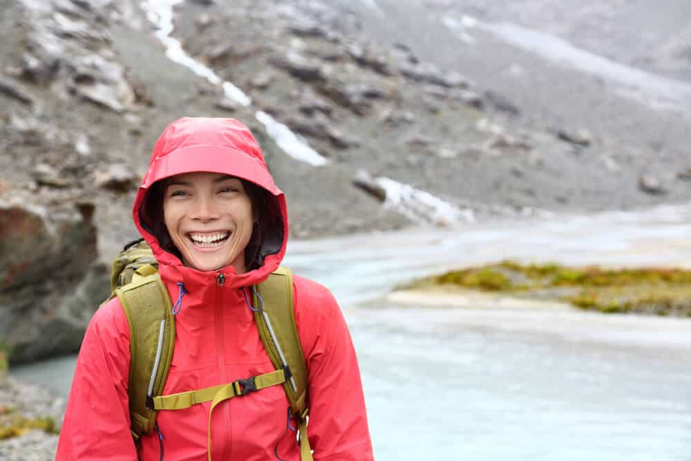 Smiling woman in rain jacket during her Iceland camping trip in September