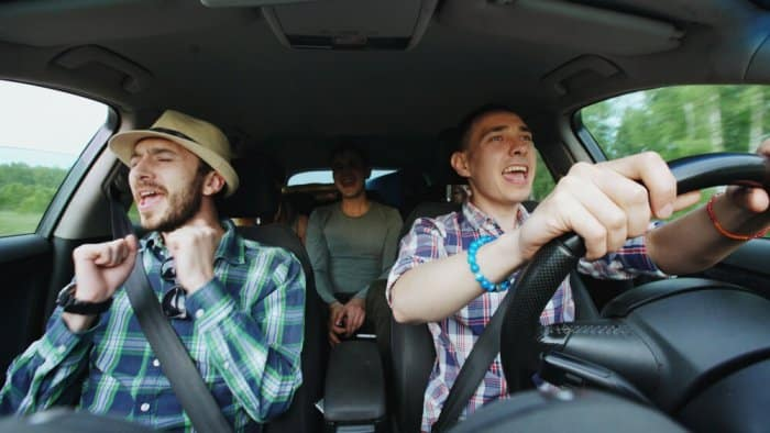 Friends in a car singing along to their road trip playlist