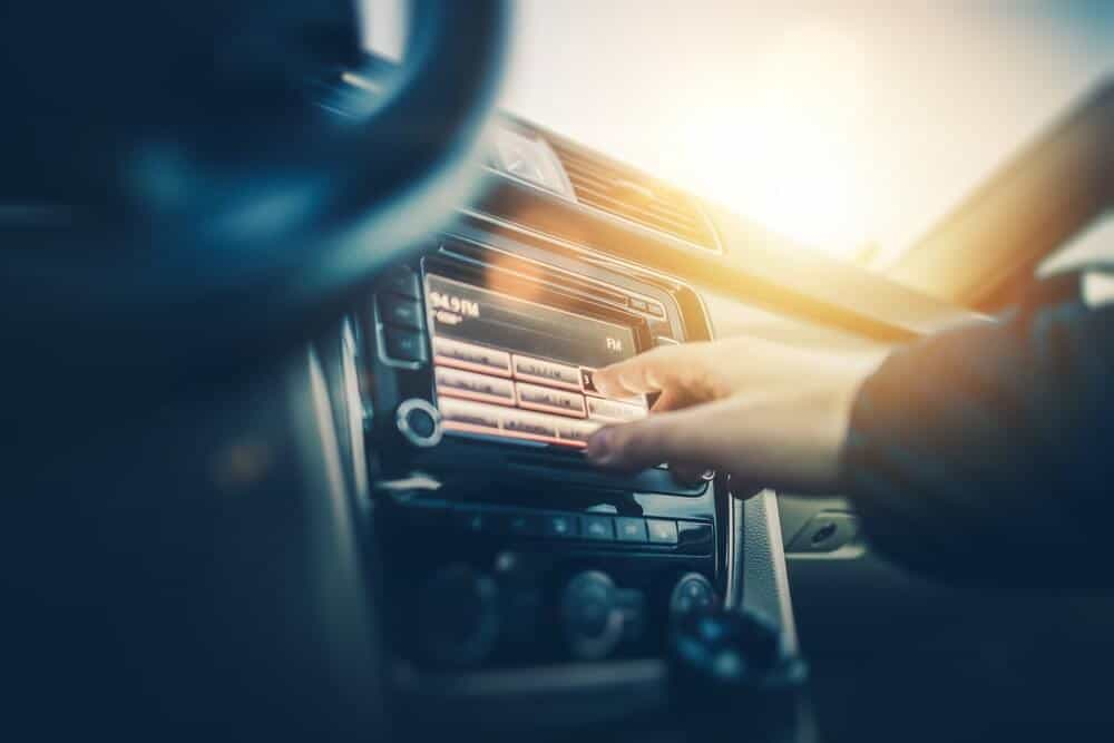 Man changing the dial on the radio to find a good road trip car song
