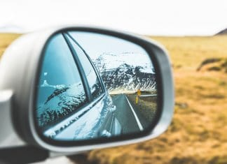 Mountains and road in car rearview mirror in Iceland with times and distances