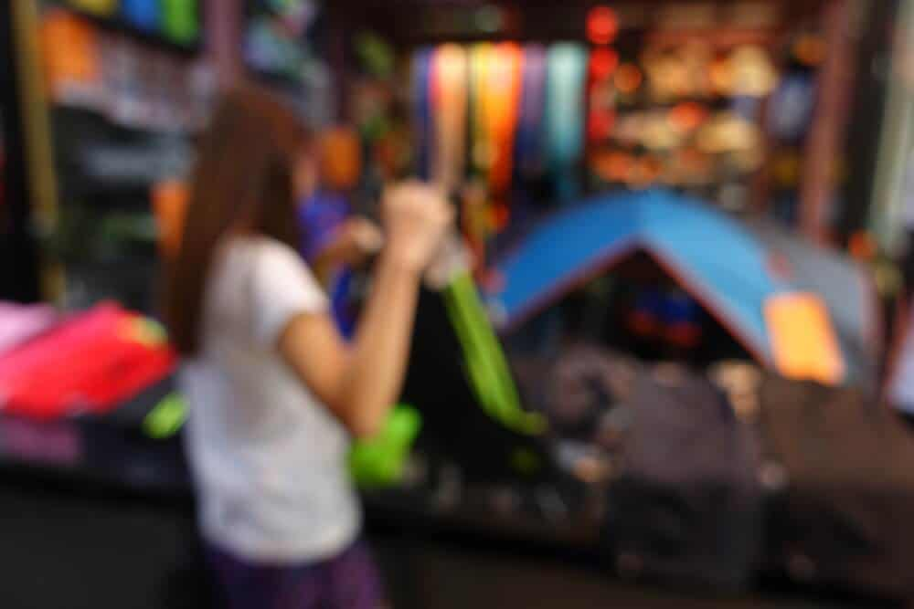 Woman choosing gear at camping equipment rental store in Iceland