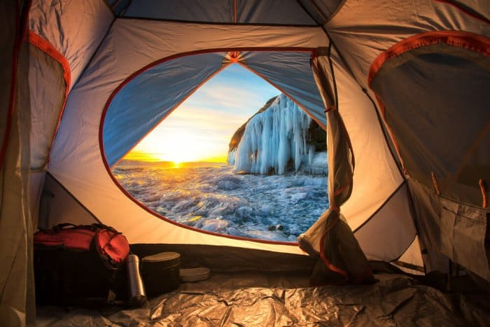 View of frozen waterfall from tent during Iceland camping trip