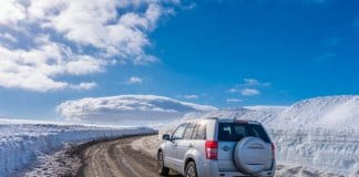 Car driving on icy, ashy, sandy roads in Iceland