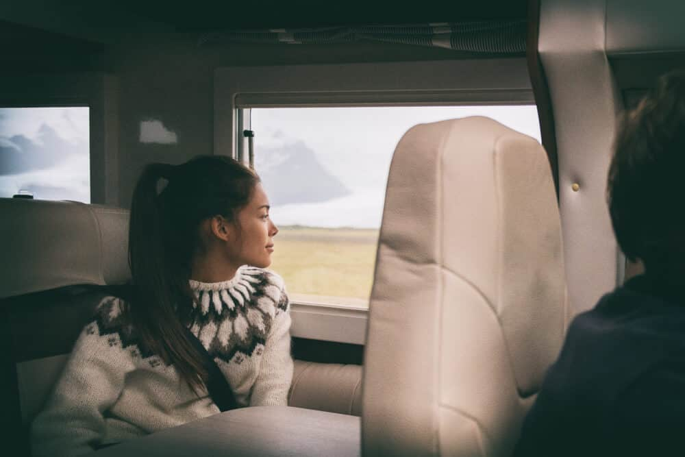 Woman in rental motorhome admiring Iceland's countryside
