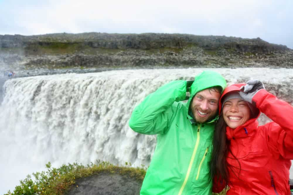 Couple in colored rain jackets enjoying Dettifoss waterfall