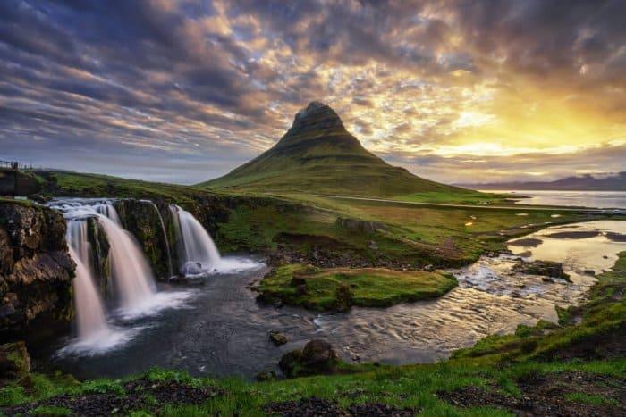 Snaefellsnes peninsula with Kirkjufell mountain and Kirkjufellsfoss waterfall illuminated sky