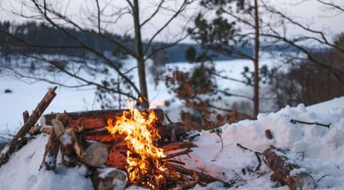 Campfire on snow during camping trip in Iceland