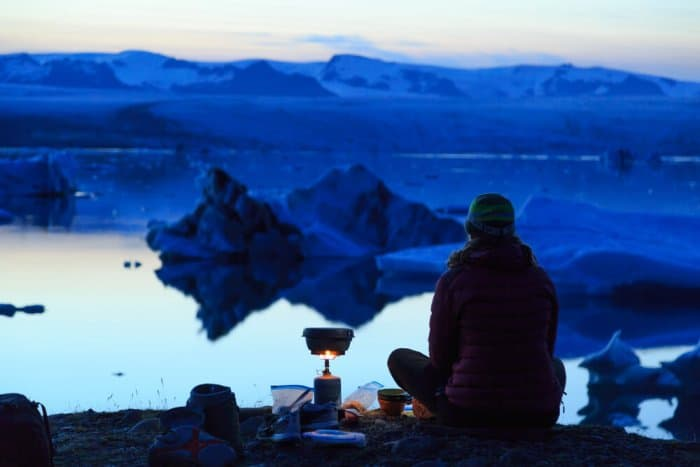 Woman cooking on her rental gas stove while camping in Iceland