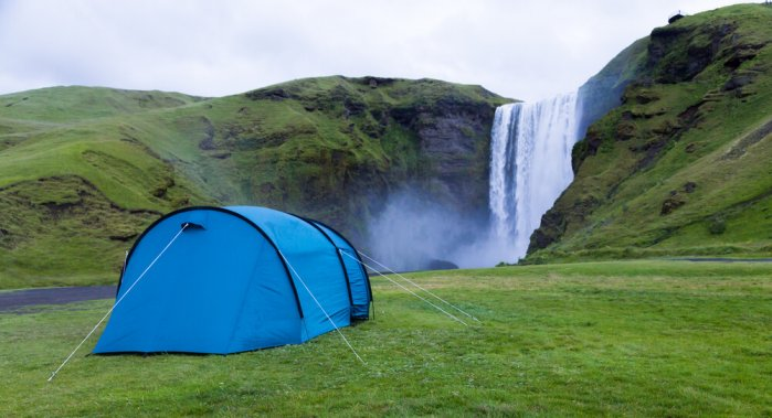 Blue tent in the designated camping area of Skógarfoss waterfall
