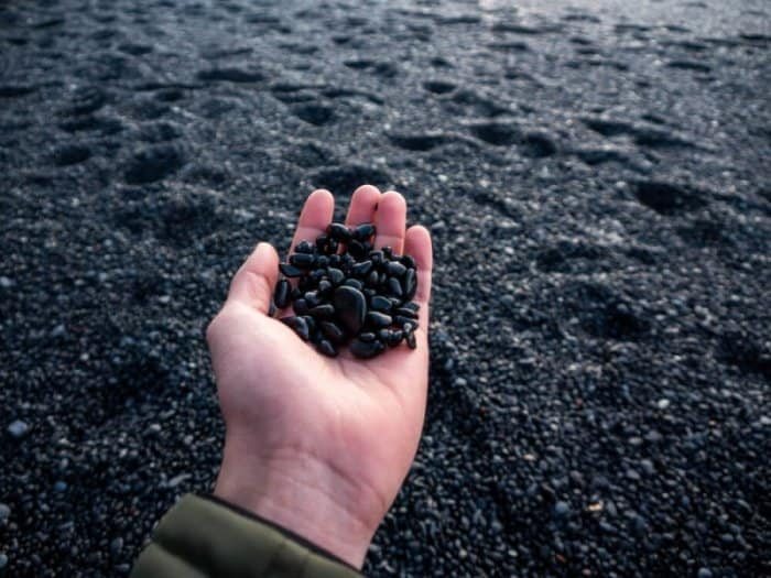 A men's hand full of pebbles from the black sand beach in Solheimasandur