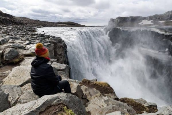A female tourist sitting at the edge of Dettifoss waterfall